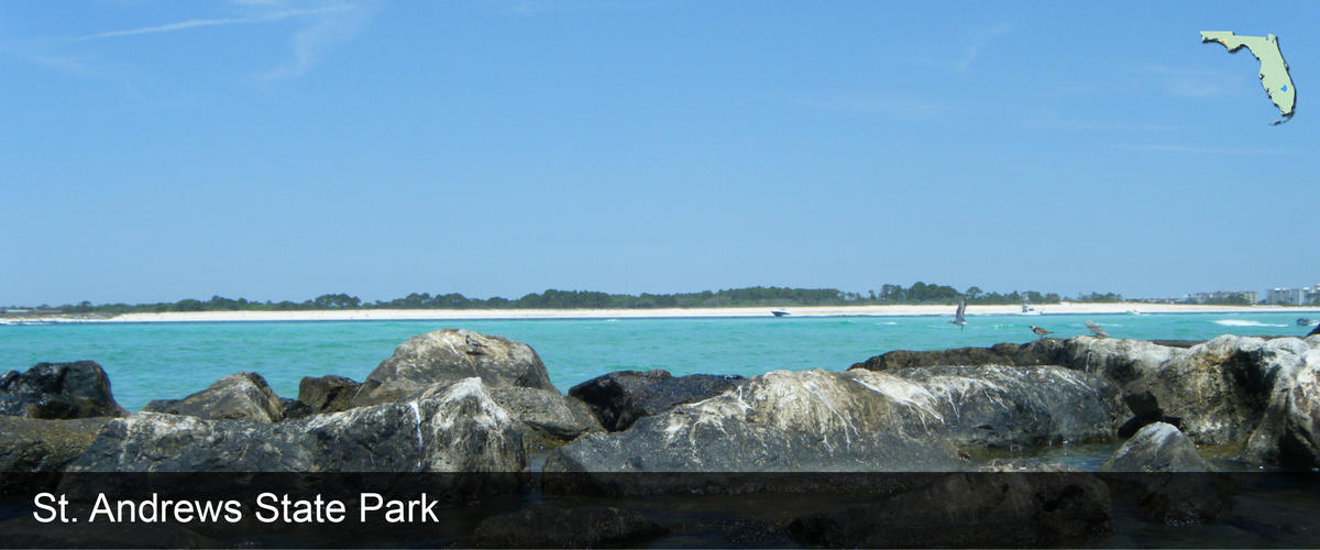 Looking over the rocks and blue water at St. Andrews State Park in Bay County, Florida
