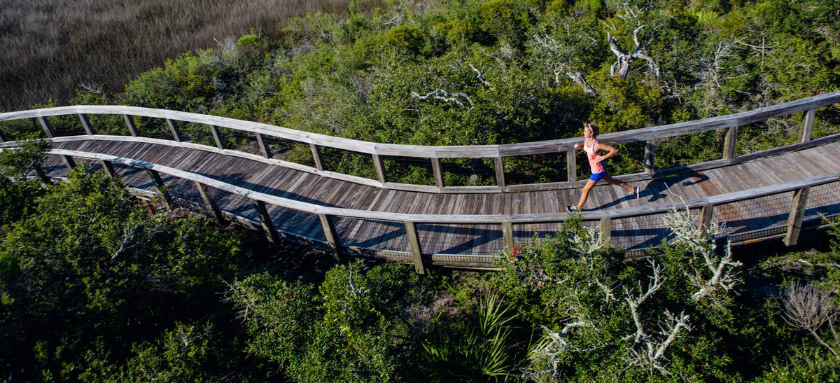 Woman running on a boardwalk at Big Lagoon State Park