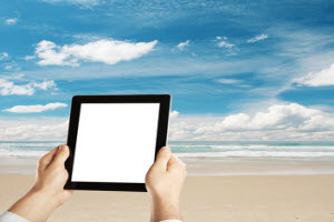 Hands holding up Tablet with Blank screen while at the beach