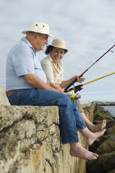 Happy senior couple sitting on rock and fishing