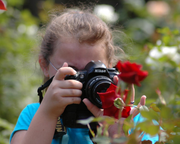 A young girl photographing a flower at Washington Oak Gardens State Park