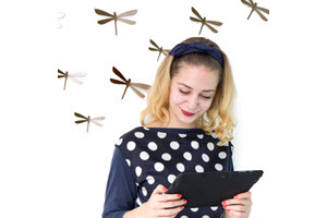 Woman reading Tablet while dragonflies fly over her head