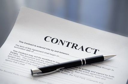 Black pen laying on top of document that says Contract