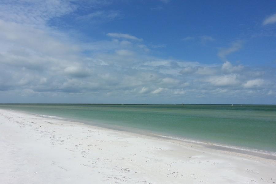 Gentle waves lap the shore of a barrier island beach in Boca Ciega Bay