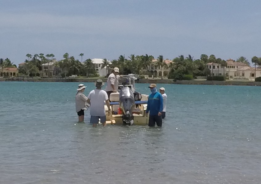 A view of people in the water beside a boat at Jupiter Inlet