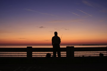 Silohouette of a man fishing from the pier at the Skyway Fishing Pier State Park