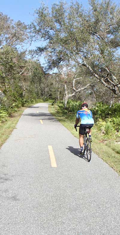 rider-on-Amelia-Island-Trail,-East-Coast-Greenway,-Doug-Alderson-vertical